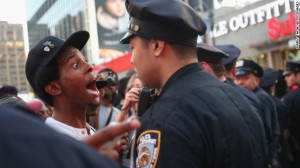 NEW YORK, NY - JULY 14:  A man argues with a police officer as Trayvon Martin supporters march while blocking traffic after a rally for Martin in Union Square in Manhattan on July 14, 2013 in New York City. George Zimmerman was acquitted of all charges in the shooting death of Martin July 13 and many protesters questioned the verdict.  (Photo by Mario Tama/Getty Images)