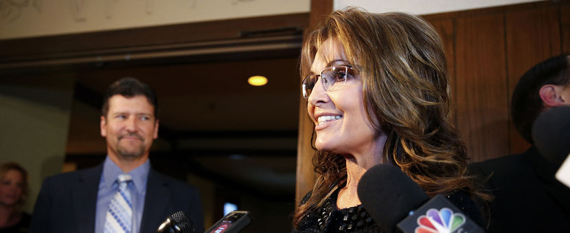 Former Republican governor of Alaska Sarah Palin speaks to members of the media as her husband Todd looks on before a celebration for evangelist Billy Graham's 95th birthday in Asheville, North Carolina November 7, 2013. REUTERS/Chris Keane (UNITED STATES)
