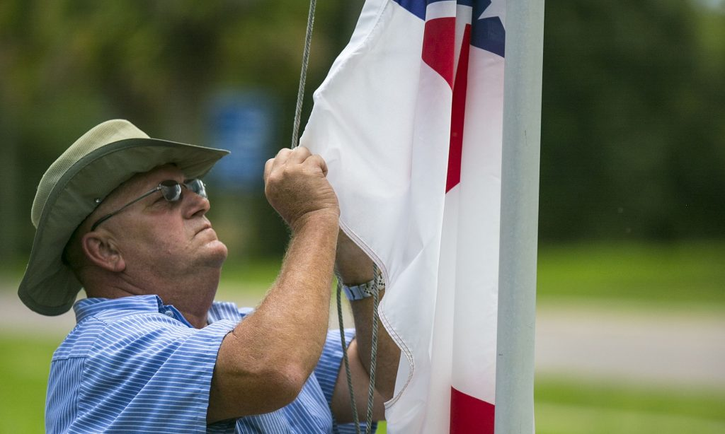 Marion County maintenance worker Vic Pollock adjusts the Confederate flag on the flag pole outside the McPherson Governmental Complex in Ocala, Fla., on Tuesday, July 7, 2015. The Marion County Commission voted Tuesday to put the flag back up after taking it down recently. (Alan Youngblood/Ocala Star-Banner via AP) MANDATORY CREDIT MAGS OUT