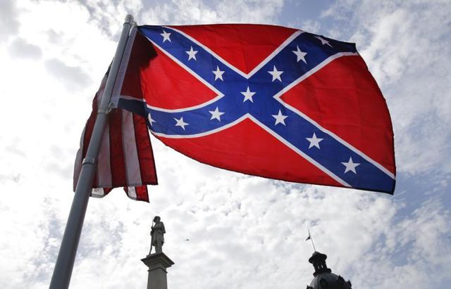 A protester waves a Confederate battle flag in front of the South Carolina statehouse, Thursday, July 9, 2015, in Columbia, S.C. More than 50 years after South Carolina raised a Confederate flag at its Statehouse to protest the civil rights movement, the rebel banner is scheduled to be removed Friday morning during a ceremony. (AP Photo/John Bazemore)