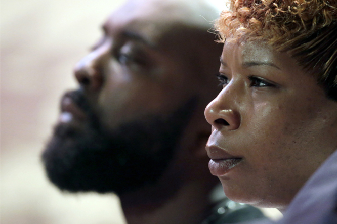 Parents of Michael Brown, Michael Brown Sr. and Lesley McSpadden listen to a speaker during a rally, Sunday, Aug. 17, 2014, for their son who was killed by police last Saturday in Ferguson, Mo. Brown's shooting in the middle of a street, following a suspected robbery of a box of cigars from a nearby market, has sparked a week of protests, riots and looting in the St. Louis suburb. (AP Photo/Charlie Riedel)